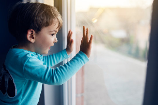 Little boy at home looking trough the window at his friends playing in the yard on the street