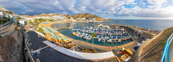 Panoramic aerial view of sea port and small bay of Puerto Rico de Gran Canaria holiday resort. Gran Canaria island, Spain