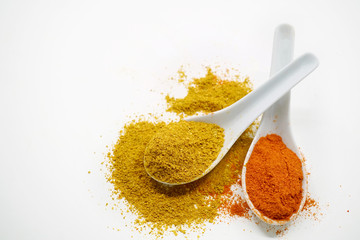 Yellow and orange ground spices, chili and curry mix on white