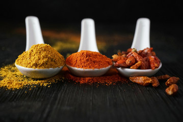 Curry and chili spices on spoons on dark wood