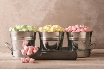 Three small pails filled with colored marshmallows with an ice cream scoop and pink marshmallows