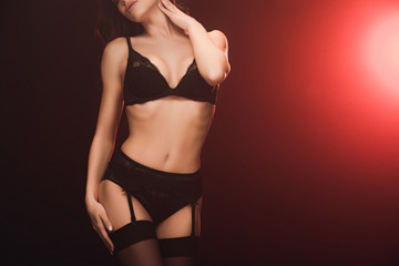 cropped view of sexy woman in lace lingerie and stockings posing on black with red light and copy space