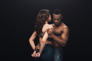 shirtless african american man hugging beautiful sexy woman in handcuffs isolated on black with copy space