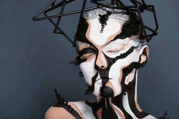 Female model with creative abstract makeup in futuristic hat