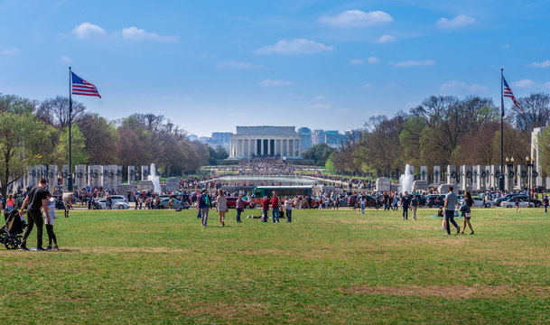 People walking toward the crowd in front of the Lincoln memorial and reflection pool in Washington DC USA on a sunny spring morning
