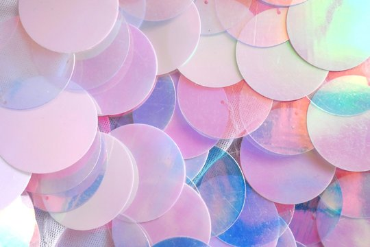 Sequins macro background.large sequins in blue and pink colors.Fabric with sequins in pastel tone.ridescent fabric.Scales background.  Background with shiny sequins.Texture scales