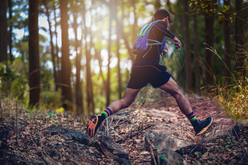 A man Runner of Trail . and athlete's feet wearing sports shoes for trail running in the forest Wall mural