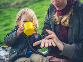 Toddler drinking from cup with his mother in nature