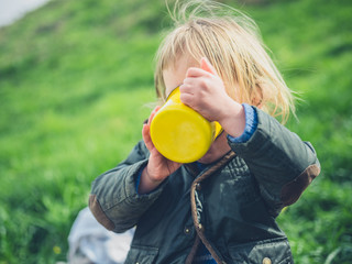 LIttle toddler drinking from cup in nature
