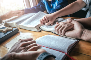 Christian group holding hands and praying together around wooden table with open bible page at home, prayer meeting concept.