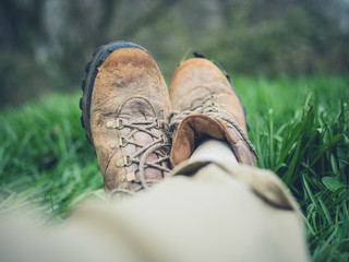 Feet of man in hiking boots resting on the grass
