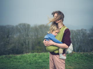 Mother with toddler in sling on windy day