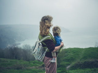Mother with toddler in sling on windy day by the sea