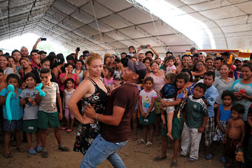 Migrant couples dance during a contest at an improvised shelter while waiting for their humanitarian visas to cross the country on their way to the United States, in Mapastepec