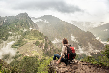 Girl-hiker looking on top of Huayna Picchu, looking on Machu Picchu