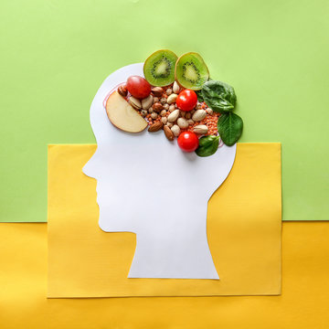 Human head with different healthy products for brain on color background