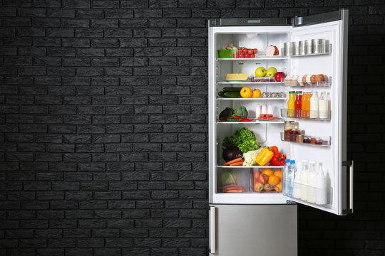 Open fridge full of food near dark brick wall