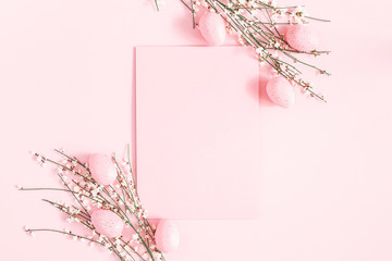 Easter composition. Easter eggs, paper blank, white flowers on pastel pink background. Flat lay, top view, copy space