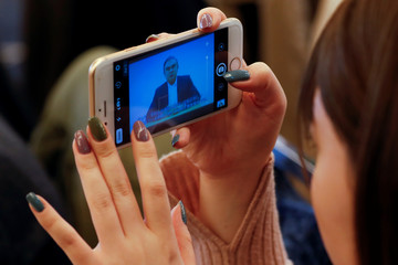 A woman takes a picture of a video statement made by the former Nissan Motor chairman Carlos Ghosn shown on a screen during a news conference by his lawyers at Foreign Correspondents' Club of Japan in Tokyo