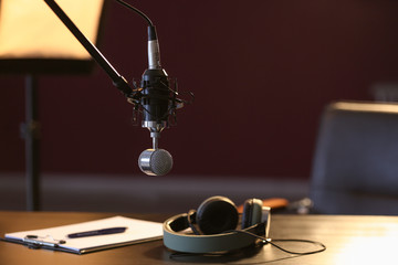 Table with headphones and microphone in radio station