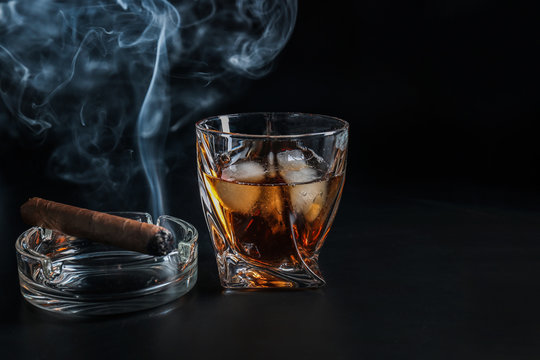 Glass of cold whiskey with cigar on dark background