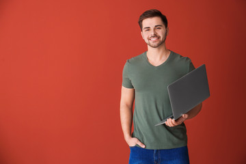 Male programmer with laptop on color background - fototapety na wymiar