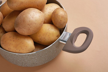 Pot with raw potato on color background
