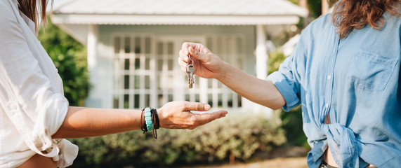 Real-estate agent giving keys to new property owners Wall mural