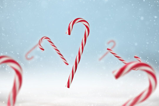 Red and white candy cane on a blue snowy background.