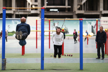 Sun and his friend Hou exercise with improvised cervical traction devices attached to high bars at a sports complex in Shenyang