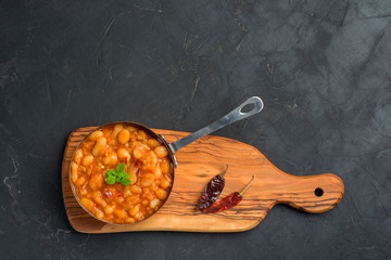 Baked beans in tomato sauce served in pan with basil and chili pepper on dark background with copy space. Flat lay