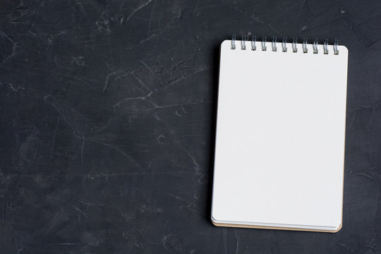 Blank notepad sheet on a dark surface. Nice mock up for designers art work.