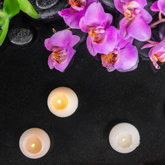 top view of spa setting with purple orchid (phalaenopsis), candles, green leaves and black zen stones with drops on water