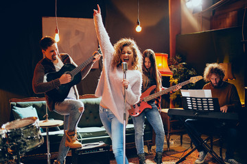 Band practice for the show. Woman with curly hair holding microphone and singing while man in background playing acoustic guitar. Home studio interior. Fotobehang