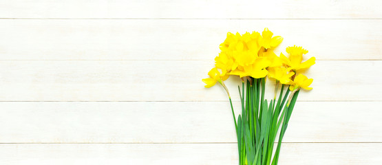 Obraz Spring floral background. Yellow narcissus or daffodil flowers on white wooden background top view flat lay. Easter concept, International Women's Day, March 8, holiday. Card with flowers copy space - fototapety do salonu