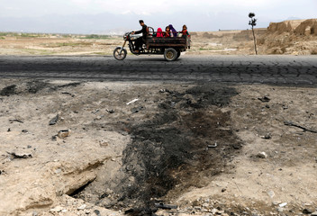 An Afghan family ride on a bike past the site of a car bomb attack near Bagram air base, Afghanistan