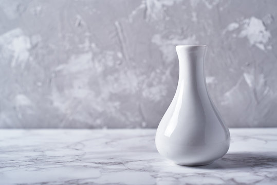 White vase isolated on plaster grey wall background, copy space. Home decor