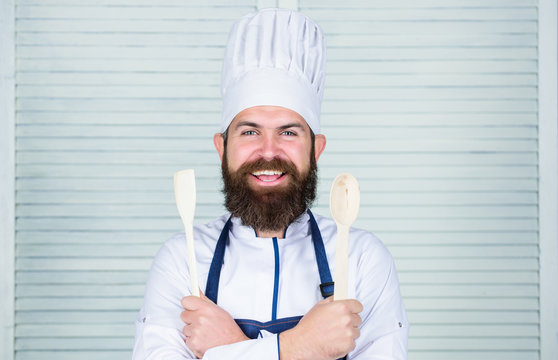 Lets try taste. Add some spices. Man with beard in cook hat and apron hold cooking tools. Cooking as professional occupation. Hipster bearded chef hold wooden spoon. Kitchenware and cooking concept
