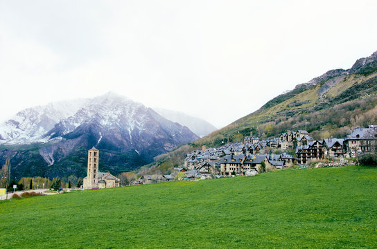 Picturesque town in a Vall de Boí,  Catalan Pyrenees, Spain. Romanesque church and snow mountains on the background