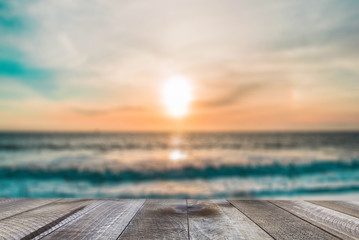 Top of wood table with blurred sea and sunset.