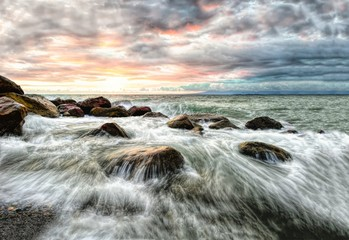 Wall Mural - Waves are breaking through rocks in this ocean seascape sunset.