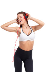Happy sporty woman singing and listening music isolated