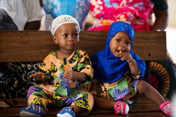 Non-identical twins Kehinde Akinbola and Taiwo Akinbola snack while waiting to receive their immunisations at the hospital in Igbo Ora