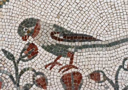 Detail of ancient colorful mosaic showing a bird