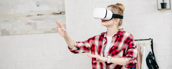 Panoramic shot of teenager in checkered shirt and vr headset