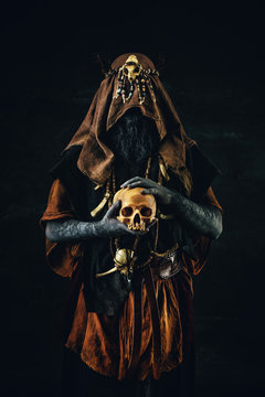 Portrait of a shaman holding a human skull in his hands