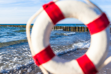 Vacation Destination Seashore / View through blurred nostalgic red white life buoy like a window to shore and row of groin at baltic sea (copy space)