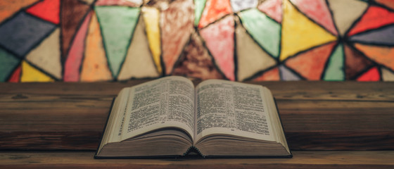 Bible on a old wooden table. Beautiful Stained-glass windows background. Religion concept..