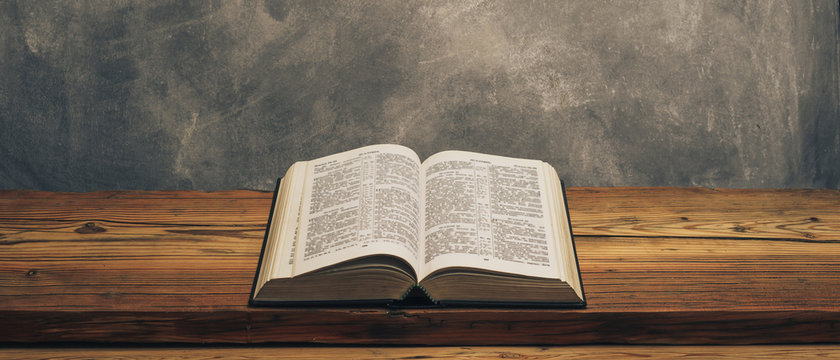 Open Holy Bible on a old oak wooden table.  Grey wall background..
