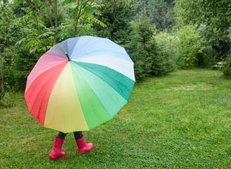 Child walks under umbrella in a rain outdoors